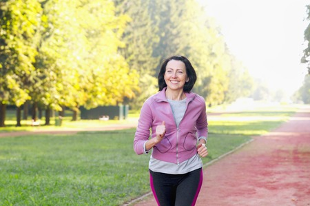 Portrait of elderly woman running in the park in early morning. Attractive looking mature woman keeping fit and healthy. Stockfoto