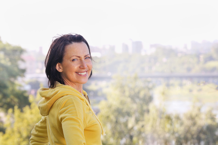 Portrait of mature woman weared in sports clothes in the park. Attractive looking mature woman keeping fit and healthy Stock Photo