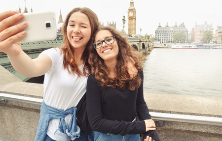 Happy smiling pretty teenage girls taking selfie at Big Ben, London. Travel and tourism concept