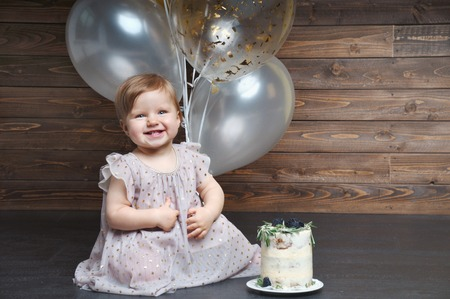 Cute smiling little girl celebrate her first birthday party with balloons and cake. Family celebration of the child. One year party. Cute infant with group of balls Stock Photo