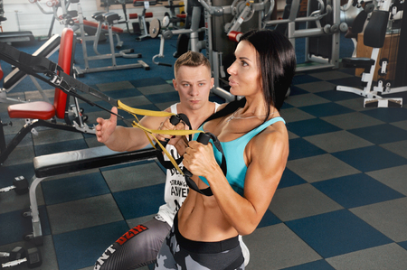 Male trainer help young fitness woman execute exercise with exercise-machine. Instructor helping young woman training on weight machine at gym