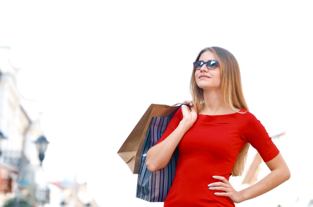 Portrait young charming long-haired woman holding shopping bags. Shopping sales and perfect mood. Design model fashion glasses.