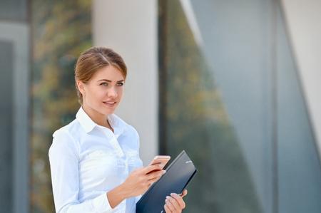 Porträt der netten jungen Frau , die Smartphone draußen verwendet . Geschäftskonzept Standard-Bild