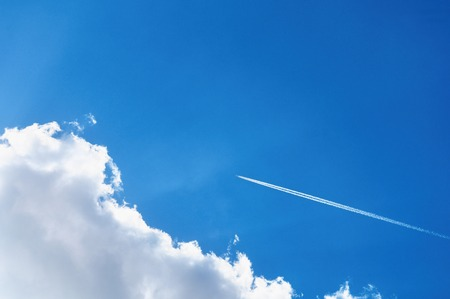 Blue sky background with a plane track. Jet of airplane in the blue sky