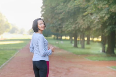 Portrait of mature woman before or after jog in the park. Attractive looking mature woman keeping fit and healthy Zdjęcie Seryjne