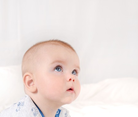 Closeup portrait of adorable newborn. Happy smiling child with blue eyes on white bed background