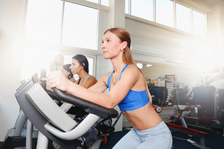 Group of four people in the gym, exercising their legs doing cardio training. Fitness young women on gym bike Zdjęcie Seryjne