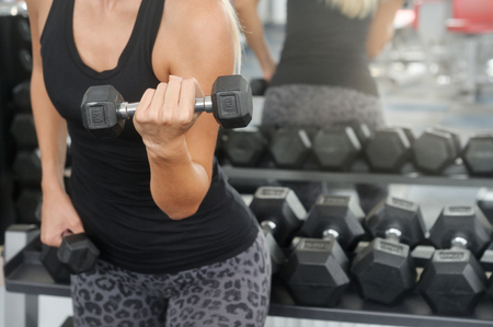 Sporty woman workout with dumbbell in gym. Healthy lifestyle and exercising. Front view