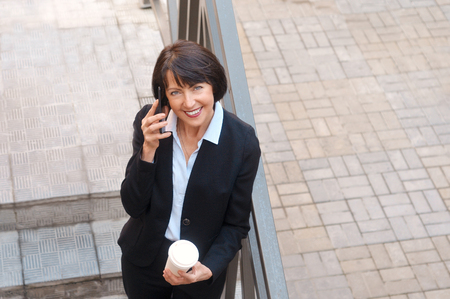 Mature businesswoman having a break in front of an office building, talking on the phone and drinking coffee. Work anywhere concept. Stock Photo