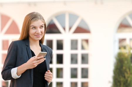 Happy businesswoman satisfies with accomplished online payment successfully on mobile looking away