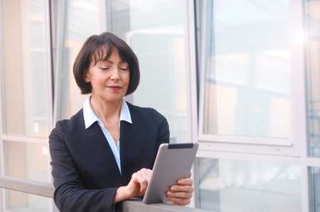 Mature businesswoman uses wireless tablet, outdoors background. Positive facial expressions. Work anywhere concept.