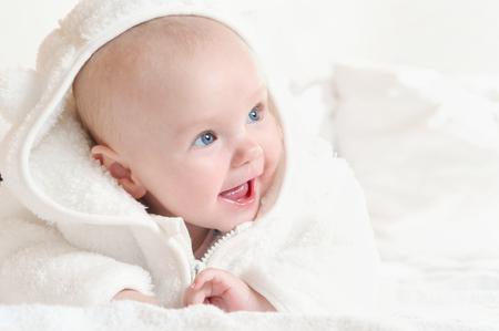 Entzückendes glückliches süßes kleines Mädchen mit breitem Lächeln, das einen weißen Bademantel trägt. Glückliches Kindheitskonzept