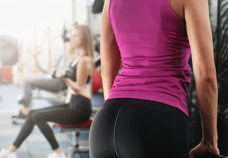 Back view of fitness woman execute exercise with exercise-machine. Another woman on background workout with dumbells