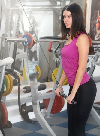 Young fitness woman execute exercise with exercise-machine. Healthy lifestyle and exercising Stock Photo