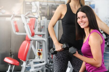 Two sporty women workout with dumbbell in gym. Healthy lifestyle and exercising.