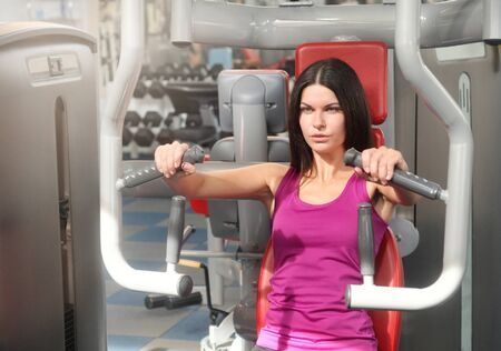 Young fitness woman execute exercise with exercise-machine. Healthy lifestyle and exercising 免版税图像