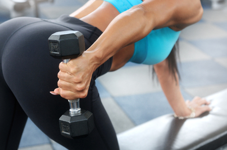 Sporty woman workout with dumbbell in gym. Healthy lifestyle and exercising. Side view