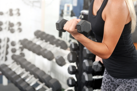 Body of sporty woman workout with dumbbell in gym. Healthy lifestyle and exercising.