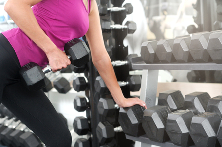 Sporty woman workout with dumbbell in gym. Healthy lifestyle and exercising. Back view