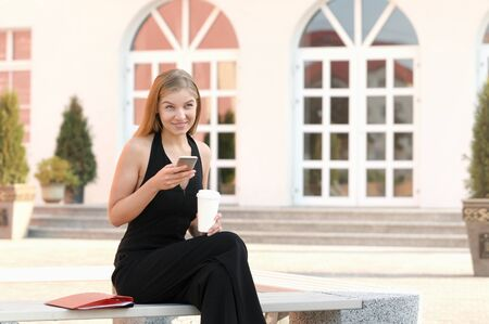 Portrait of young businesswoman using mobile phone and drinking coffee on a break at outdoor
