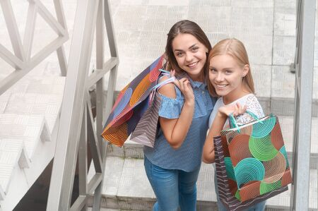 Beautiful girls with shopping bags stand on stairs in city street. Lifestyle, friendship and people concept. Top view
