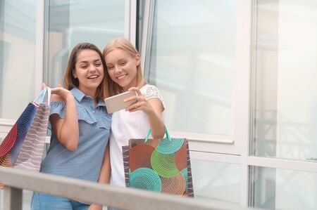 Two beautiful young women taking a selfie with their cell phone. Lifestyle, friendship and people concept 免版税图像