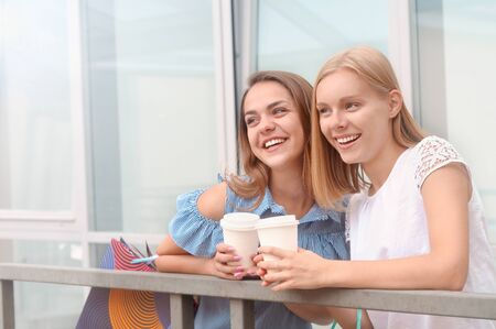 Attractive young women with take away coffee in summer city. Lifestyle, friendship and people concept