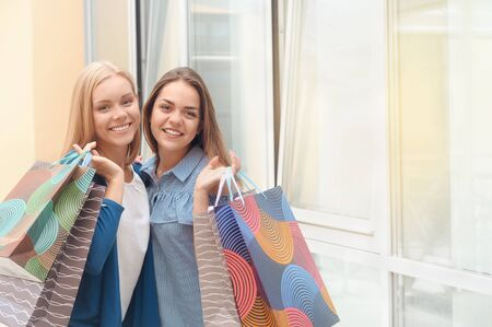 Two young pretty stylish women holding the shopping bags and looking forward in a good mood. Happy shopping with smiles. Perfect shopping 免版税图像