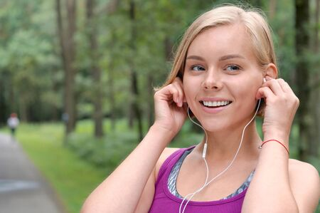 Close up portrait of young smilling sporty woman running with headphones in the fores outdoor. Healthy lifestyle concept 免版税图像