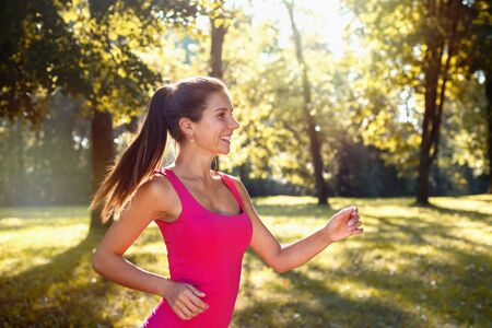 Portrait of young smilling sporty woman running in the park outdoor. Healthy lifestyle concept