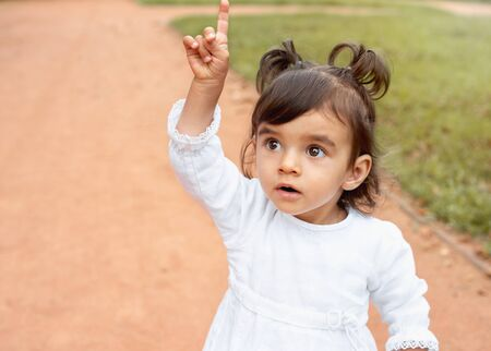 Little amazed baby girl pointing finger up in the park. Happy childhood concept