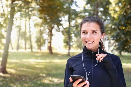 Portrait of young smilling sporty woman running with headphones in the park outdoor. Healthy lifestyle concept 免版税图像