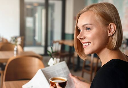 Young blonde woman having a breakfast with coffee reading newspaper in cafe. Happy lifestyle concept.