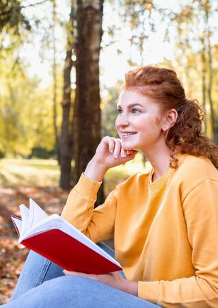 Smiling happy red hair student girl reading a book outside in autumn park. Study students conceprt. 免版税图像