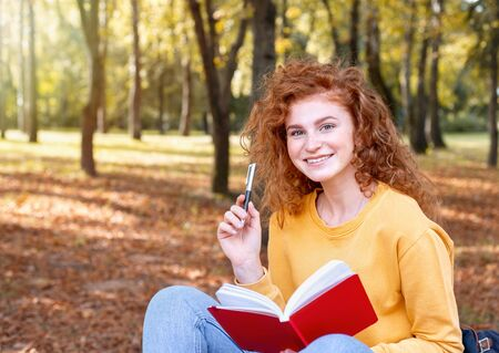 Smiling happy red hair student girl taking a note outside in autumn park. Study students conceprt.