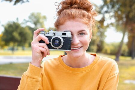 Smiling happy red hair student girl taking picture with old vintage camera outside in autumn park. Study students conceprt. 免版税图像