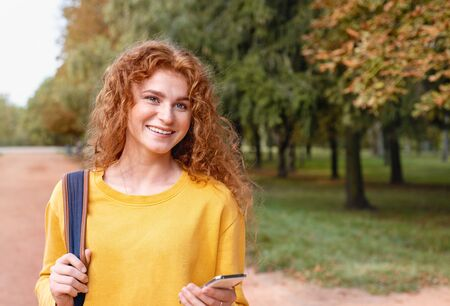 Smiling happy red hair student girl with phone outside in autumn park. Study students conceprt.