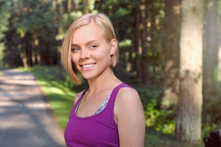 Portrait of young smilling sporty woman running in the fores outdoor early in the morning. Healthy lifestyle concept