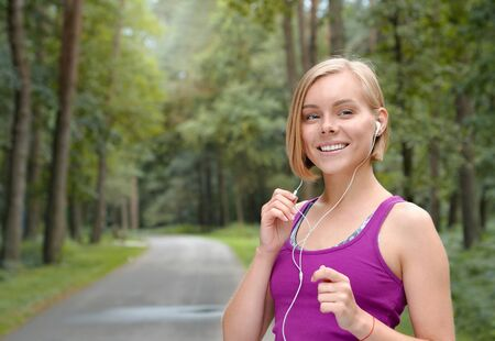 Portrait of young smilling sporty woman running with headphones in the fores outdoor. Healthy lifestyle concept