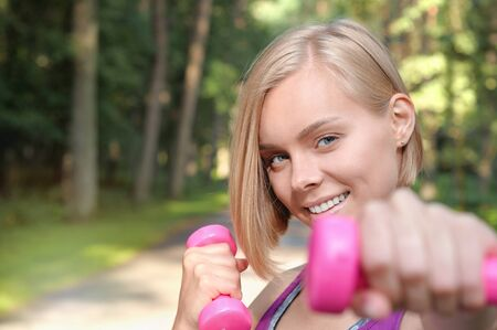 Portrait of young blonde woman working out with dumbbells outdoor. Healthy lifestyle concept.