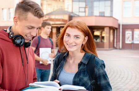 Smiling red hair teenager girl reading a classbook with her group mate against background of the university. Education concept