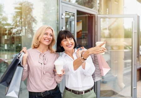 Two mature women having fun while doing shopping and drinking coffee. Pastime concept of mature people 免版税图像