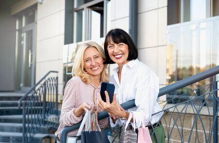 Two mature women with phone having fun while doing shopping. Pastime concept of mature people