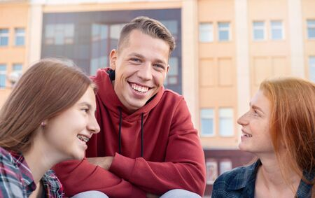 Portrait of happy smiling teenage boy chatting with girls while studying outdoors near university. Education concept