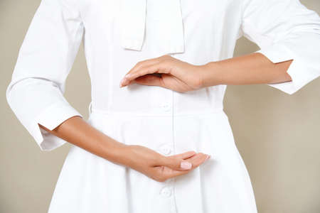 Close up cropped photo of woman's slim stomach with her hands showing a balance in microflora in a white robe. Healthy eating concept.