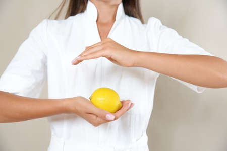 Close up photo of woman's hands in circle with lemon in a white robe. Healthy eating concept.