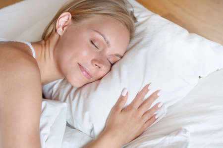 Beautiful young blonde woman sleeping near the window in a white bed. Self care lifestyle concept
