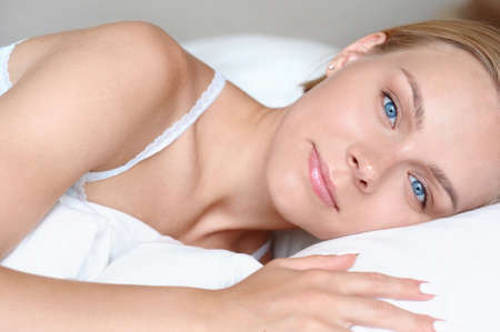 Close up portrait of beautiful young blonde woman waking up in the morning in a white bed. Self care lifestyle concept