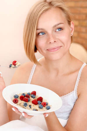 Beautiful young blonde woman eating her oatmeal with berries for breakfast in the morning. Healthy lifestyle concept 免版税图像