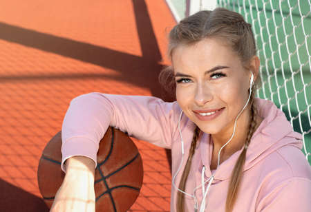 Portrait of confident young sporty woman wearing pink hoodie holding basketball on outdoor court. Healthy lifestyle concept.